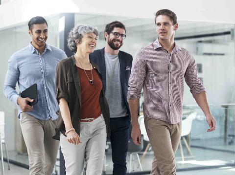 Grupo de jóvenes paseando en la oficina pensando en contratar un plan de pensiones