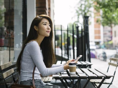 Una turista china toma un café en una terraza
