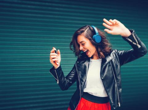 Chica escuchando musica con sus auriculares y el movil