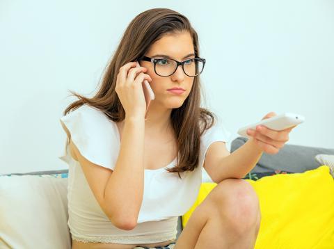 Chica con un teléfono móvil y un mando a distancia