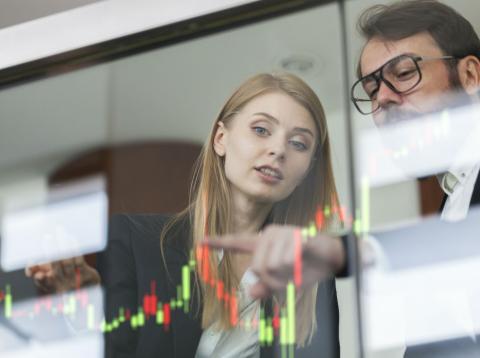 Un hombre y una mujer analizan datos en una pantalla