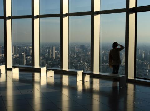 Mujer mirando a una ciudad desde un rascacielos.