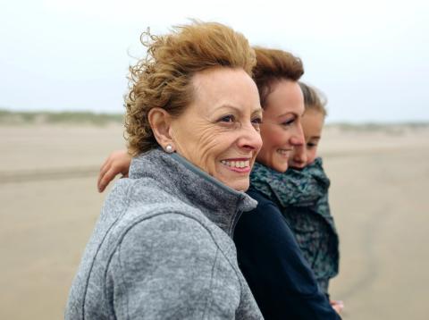 Una mujer pasea por la playa junto a su hija y su nieta