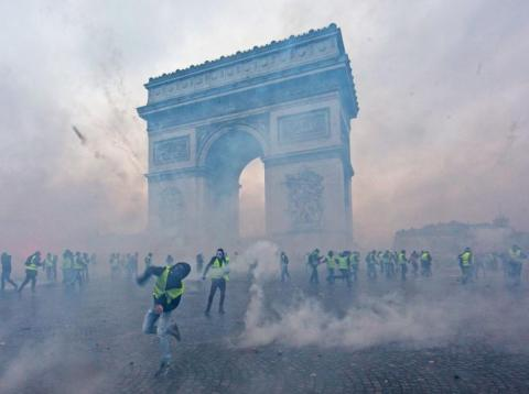 Teargas surrounds protesters as they clash with riot police during a 'Yellow Vest' demonstration near the Arc de Triomphe in Paris on Saturday.