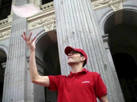 Un trabajador de Telepizza ante la Bolsa de Madrid