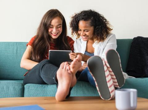 Amigas en el sofá mirando ipad