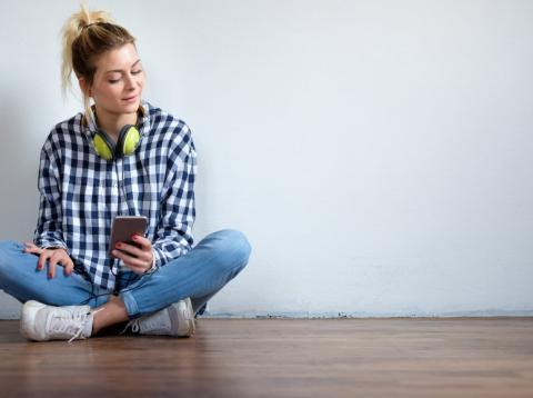 Una chica joven sentada con un teléfono móvil en las manos