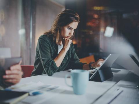 Una trabajadora preocupada consulta los datos de su empresa