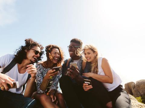 Cuatro millennials se ríen mientras se relacionan con sus smartphones