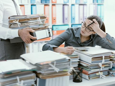 Una mujer mira con recelo el montón de documentos que le entrega su jefe