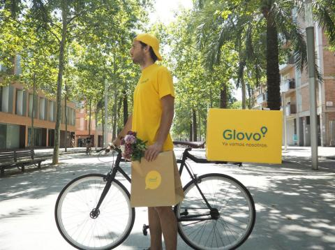 Un repartidor de Glovo con un pedido en la mano