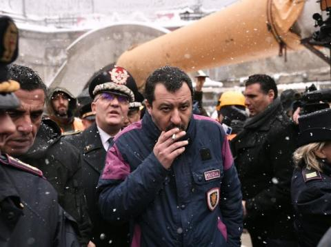 Italy's Interior Minister and deputy PM Matteo Salvini (C) smokes a cigarette during a visit to the building site of the TAV high-speed train line between Italy and France, on February 1, 2019 in Chiomonte, northwestern Italy. -