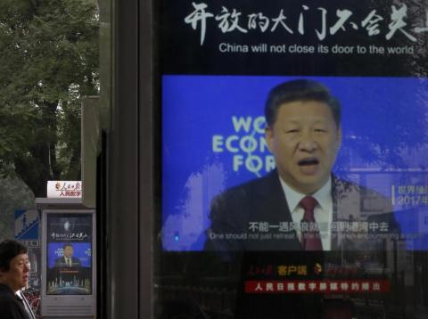 A man walks by electronic display panels advertising a video footage of Chinese President Xi Jinping speaking at the World Economy Forum on a street in Beijing, Monday, June 25, 2018.