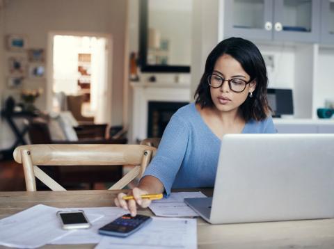 Una mujer hace cuentas ante su ordenador