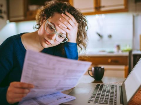 Una joven examina un documento con preocupación