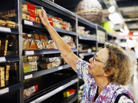 Señora comprando galletas en el supermercado