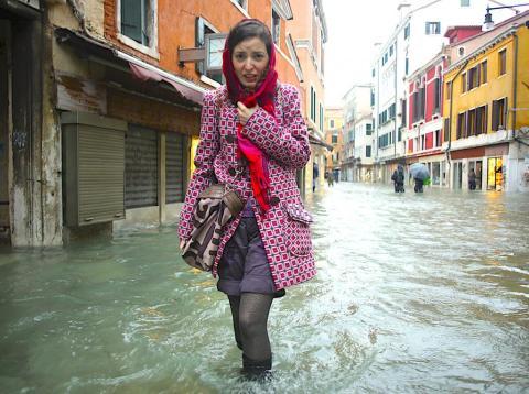 Una mujer intenta caminar por una calle inundada en Venecia.