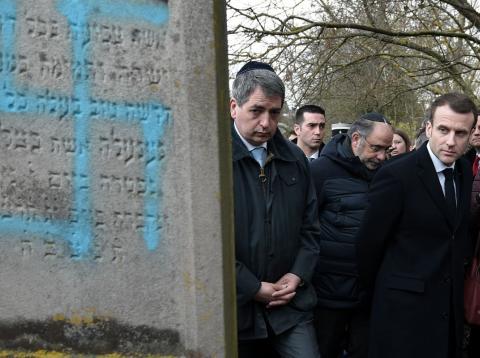 Emmanuel Macron pasa junto a una lápida hebrea con una hesvástica pintada