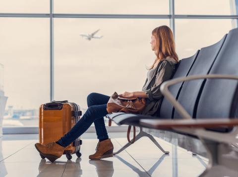 Una mujer espera con sus maletas en un aeropuerto