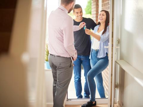 Un agente inmobiliario entrega a una pareja las llaves de su nueva casa