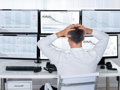 Un trader se lleva las manos a la cabeza por las pérdidas en sus inversiones