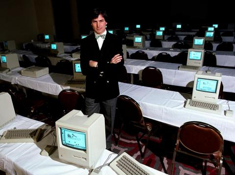 Late Apple CEO Steve Jobs surrounded by Macintosh computers.
