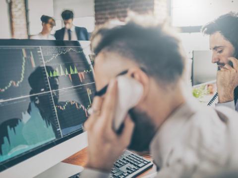 Trabajadores de un fondo de inversión atienden a sus clientes ante el ordenador