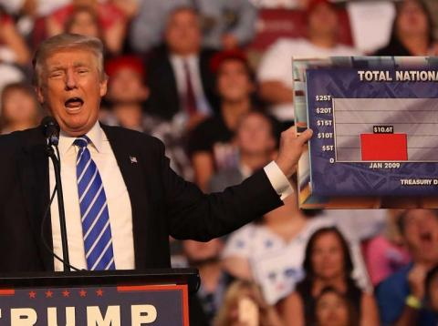 President Donald Trump holds up a chart showing the US national debt during a campaign rally in 2016.