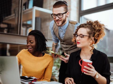 Tres jóvenes en prácticas en una empresa