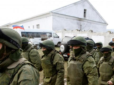 Armed men, believed to be Russian servicemen, walk outside a Ukrainian military base in Perevalnoye, near the Crimean city of Simferopol, March 14, 2014.