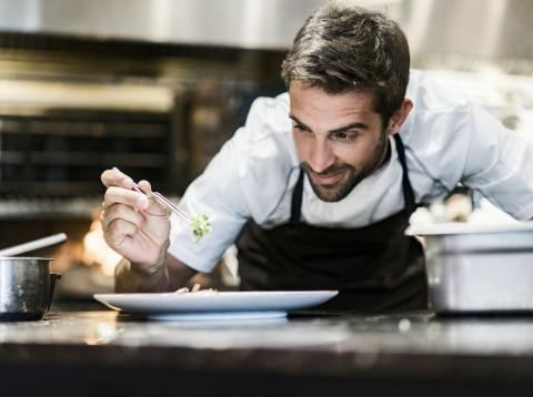 Un cocinero prepara un plato