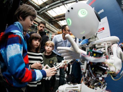 Un grupo de niños juega con un robot de Inteligencia Artificial