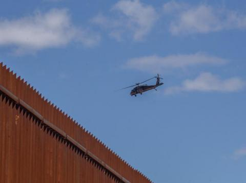 A Helicopter from the Customs and Border Protection Office flies over the US-Mexico Border wall on April 5, 2019 in Mexicali, Mexico.