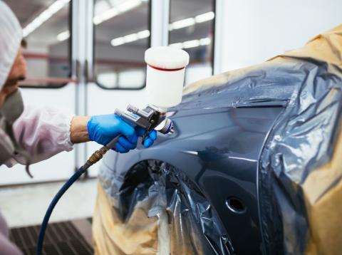 Un operario pinta la carrocería de un coche