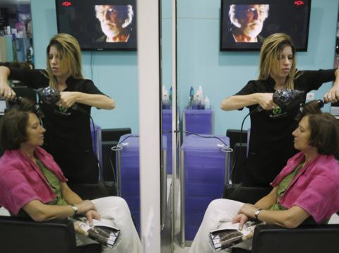 Una peluquera atiende a una clienta en un salón de belleza en Ronda (Málaga).