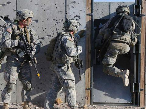 US soldiers conduct breaching operations in a mock-urban environment.