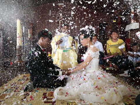 Una novia y un novio en Camboya celebran su boda en una iglesia católica.