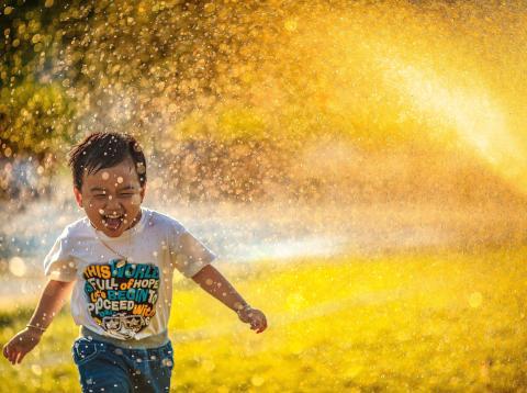 Un niño pequeño jugando con un aspersor de agua