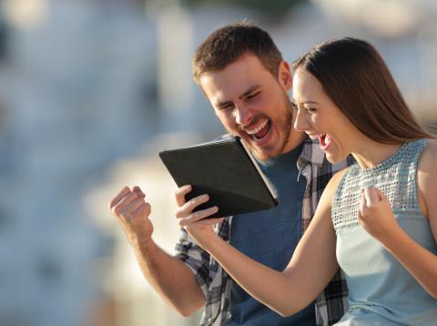 Una pareja comprueba una apuesta deportiva en su teléfono móvil.