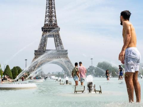 Tourists and Parisians bathe at the foot of the Eiffel Tower in the water of the Trocadero fountain to cool down on June 24, 2019.
