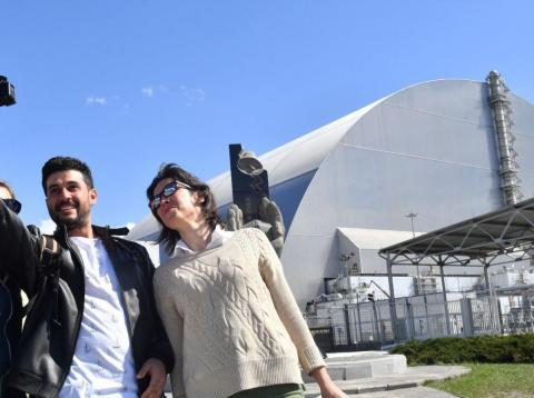 Tourists take a photo in front of the contained reactor site.
