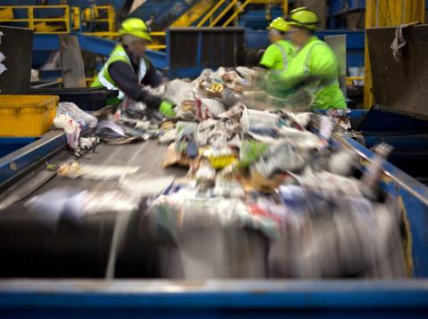 Trabajadores en una cinta de separación de residuos en una planta de reciclaje