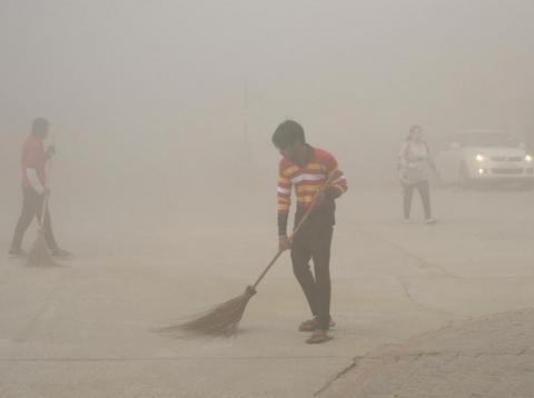 Trabajadores indios usan escobas para barrer el polvo en la niebla matutina en el Gran Noida, cerca de Nueva Delhi, India, el 10 de noviembre de 2017.