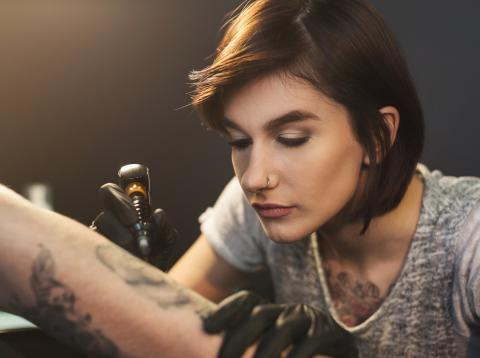 Chica haciendo un tatuaje