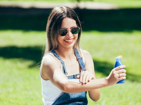 Chica usando una crema solar