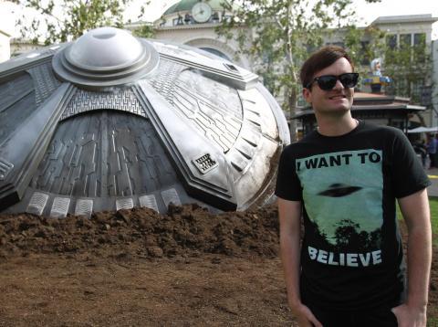 "Fan wears ""I want to believe"" t-shirt in front of UFO model for Fox's ""The X-Files"" UFO episode."