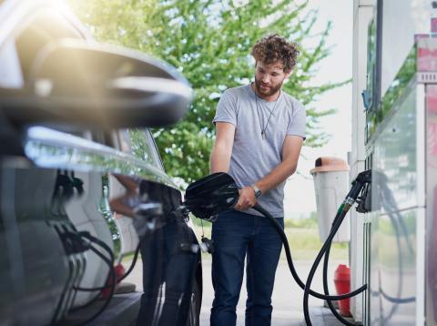 Hombre en la gasolinera llenando el depósito de su coche de combustible