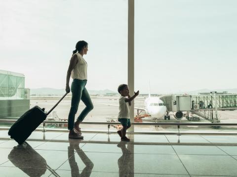 Una mujer espera con un niño en el aeropuerto.