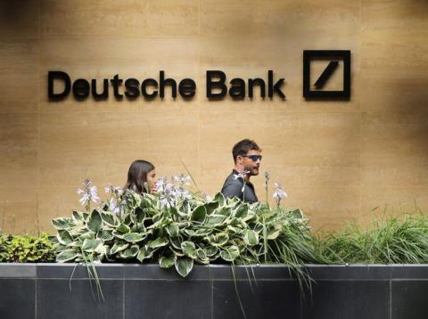 People walk past a Deutsche Bank office in London