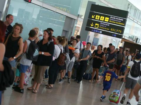 Viajeros hacen cola durante una huelga de personal de seguridad en el aeropuerto de Barcelona